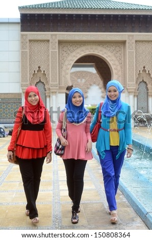 Young asian muslim student in head scarf smile while walking  - stock photo