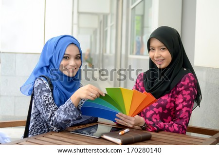 Young asian muslim woman in head scarf discuss palette of colors designs for interior works - stock photo