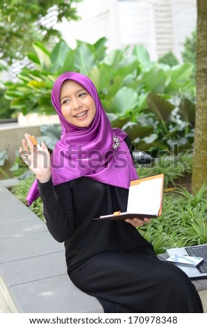 Young asian muslim woman in head scarf happy reading at park - stock photo