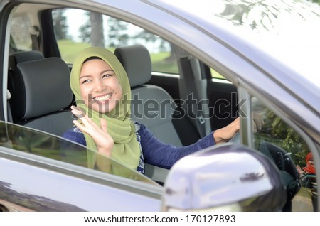 Young asian muslim woman in head scarf smile inside the car wave hand to friend