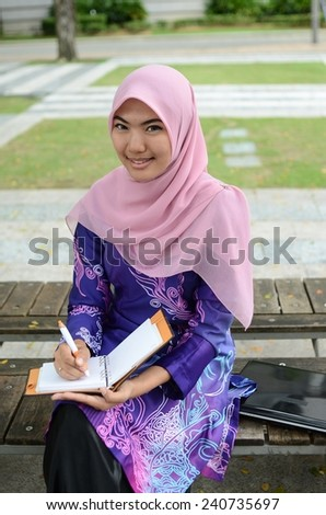 Young asian muslim woman in head scarf smile reading a book
