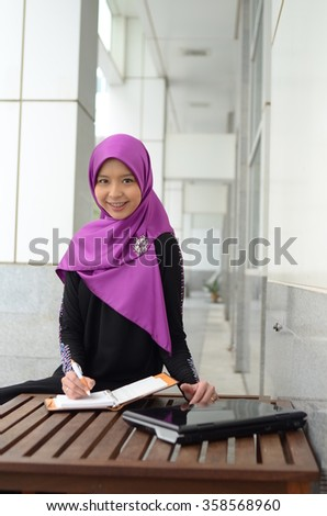 Young asian muslim woman in head scarf smile reading a book  - stock photo