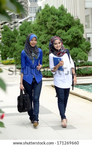 Young asian muslim woman in head scarf smile walking outdoors and looking very happy - stock photo