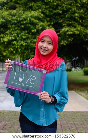 Young asian muslim woman in head scarf smile while holding love green board - stock photo