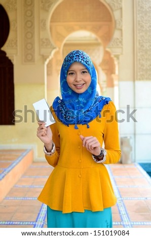 Young asian muslim woman in head scarf smile while holding white box - stock photo