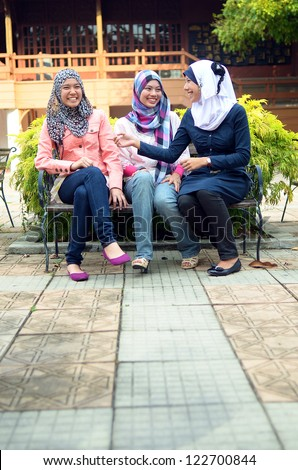 Young asian muslim woman in head scarf smile while sitting together - stock photo