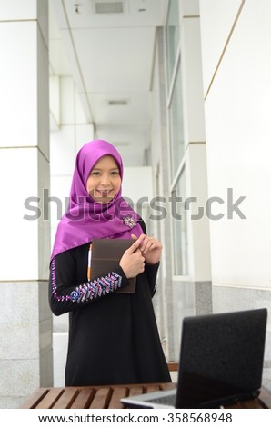Young asian muslim woman in head scarf smile with laptop - stock photo