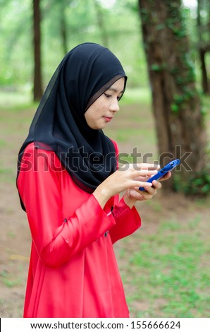 Young asian muslim woman in head scarf smile with mobile phone