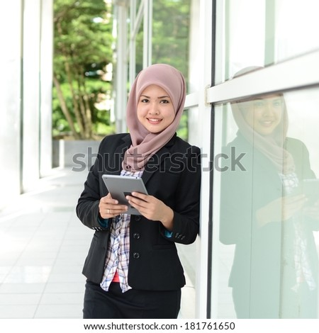 Young asian muslim woman in head scarf smile with mobile tablet