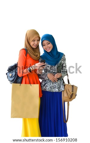 Young asian muslim woman in head scarf with shopping bag - stock photo