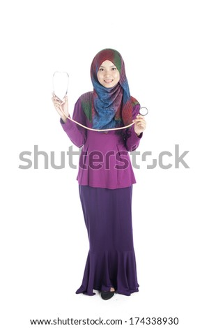 Young asian muslimah (woman) doctor in head scarf  holding a stethoscope.