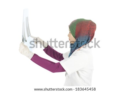 Young asian muslimah (woman) doctor in head scarf holding a x ray film.