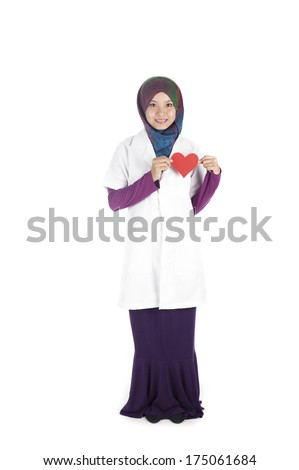 Young asian muslimah (woman) doctor in head scarf wearing white coat holding  red heart symbol.