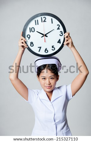 Young Asian nurse show a clock over her head on gray background