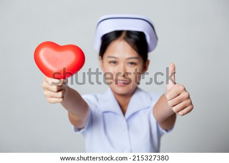 Young Asian nurse thumbs up with red heart on gray background