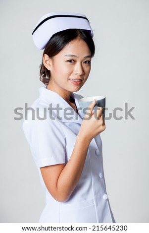 Young Asian nurse with a cup of coffee on gray background