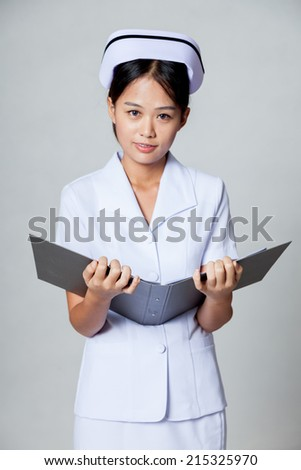 Young Asian nurse with a folder on gray background