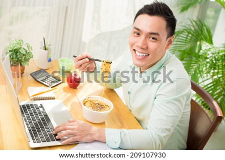 Young Asian office worker eating instant noodle while working on laptop - stock photo