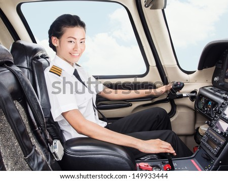 Young Asian pilot student in her uniform flying light craft plane in the sky - stock photo