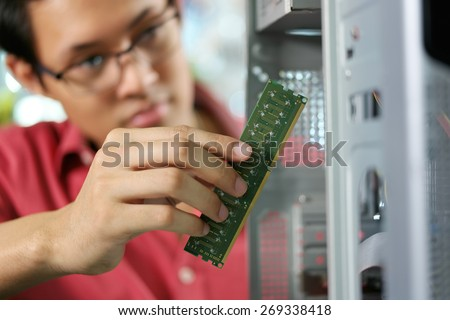 Young asian shop owner working in computer store, repairing computer and adding ram to pc. Focus on hand holding bank of RAM - stock photo