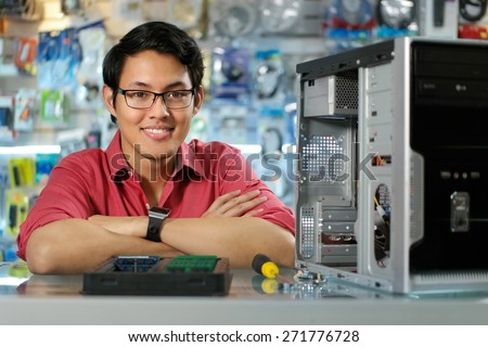 Young asian shop owner working in computer store, repairing computer and adding ram to pc. Portrait of man smiling at camera - stock photo