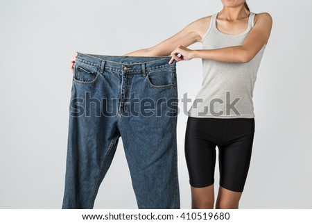 Young asian slim woman showing too big jeans, isolated on background - stock photo