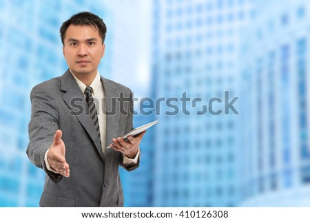young asian smiling handsome business man standing at modern office - stock photo
