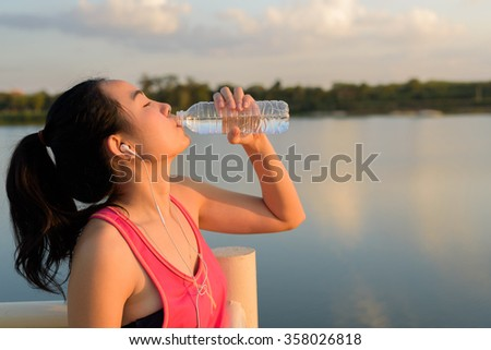 Young Asian sporty woman drinking water during jogging - stock photo