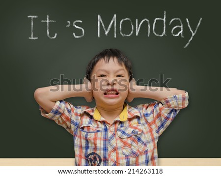 """Young Asian student covering ears in front of chalk board with """"It's Monday"""" message - stock photo"""
