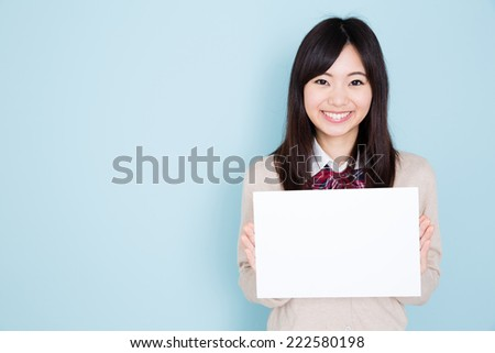 young asian student isolated on blue background - stock photo
