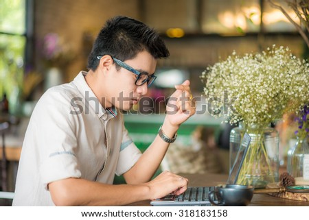 Young asian student man using tablet computer in cafe, working on laptop - stock photo