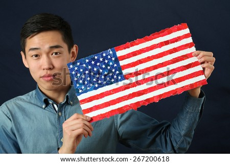 Young Asian student showing US national flag and looking at camera
