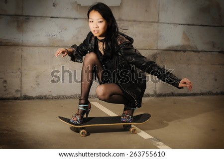 Young asian teen riding a skateboard - stock photo