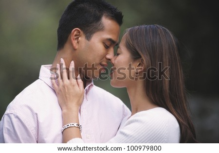 Young Asian touching noses outdoors - stock photo