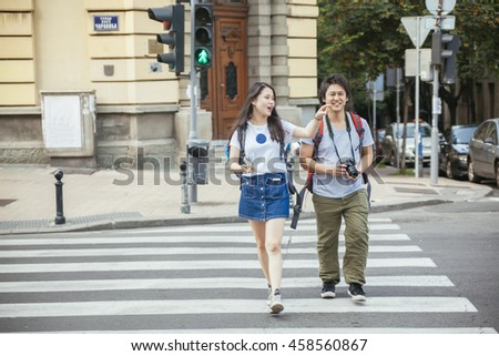Young Asian Tourists Crossing The Street