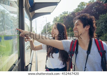 Young Asian Tourists Waiting For A Bus