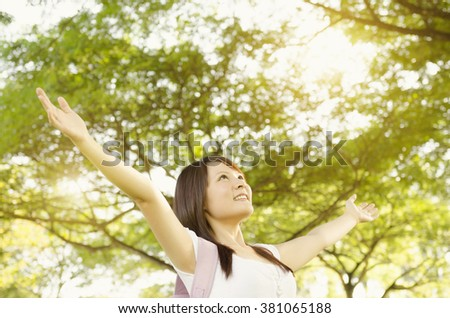 Young Asian university girl student standing on campus lawn, open arms and smiling. - stock photo