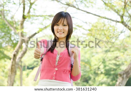 Young Asian university girl student standing on campus lawn, showing thumb up and smiling. - stock photo