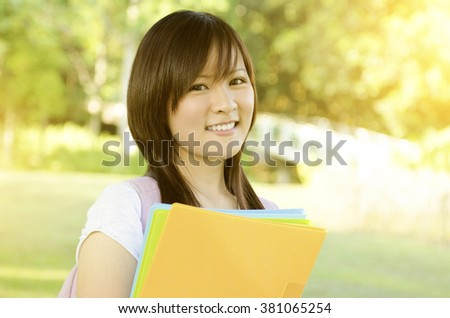 Young Asian university student standing on campus lawn, holding file folder and smiling. - stock photo