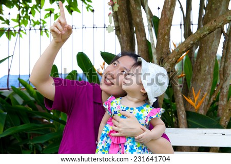 Young asian woman and cute little daughter happily in the backyard,mother pointing up - stock photo