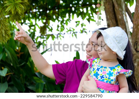 Young asian woman and cute little daughter  smiling happily in the backyard,mother pointing up - stock photo