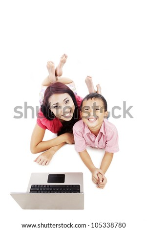 Young asian woman and her son lying on the floor with laptop computer shot in studio isolated on white - stock photo