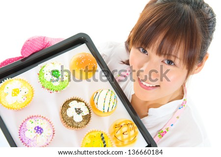 Young Asian woman baking bread and cupcakes, wearing apron and gloves holding tray isolated on white. - stock photo
