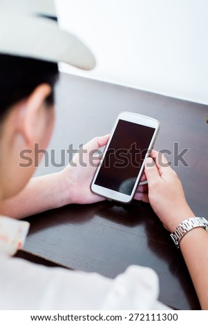 Young  asian woman casual look and hat using a touchscreen smartphone -shallow depth of field - stock photo