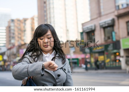 Young Asian woman checking her watch on a street in a large city - stock photo
