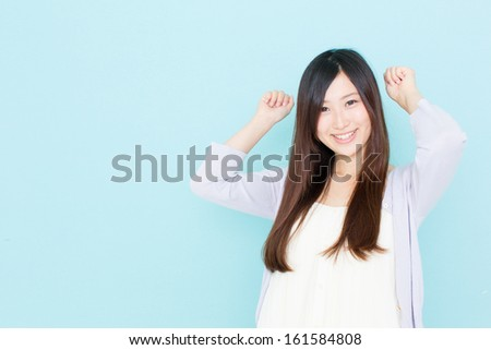 young asian woman cheering on blue background - stock photo
