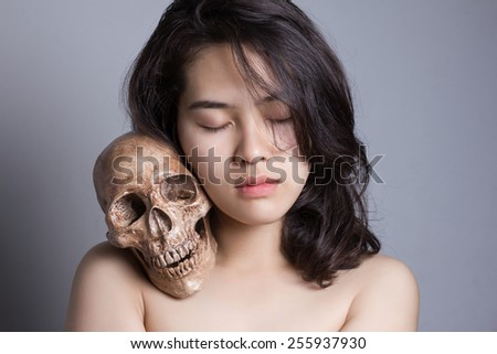 Young Asian woman close her eyes with skull on her shoulder. - stock photo