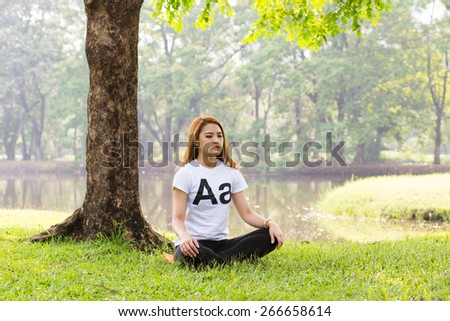 Young asian woman doing yoga in the Lotus position at the green natural park - stock photo