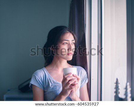 Young Asian woman drinking coffee in her apartment