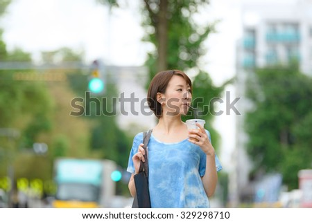 Young Asian woman drinking ice coffee and walking on a street. - stock photo